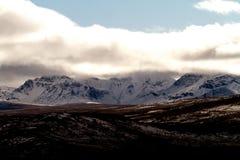 Wolken die Snowcapped Bergen overspoelen Stock Foto