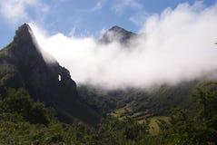 Wolken durch Berge Stockfotografie