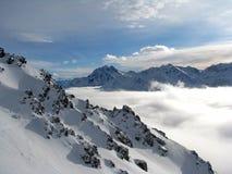 Wolken in een vallei in Alpen Stock Afbeeldingen
