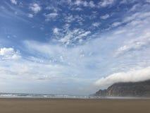 Wolken an einem Ozeanstrand Stockbild