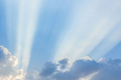 Wolken en een blauwe hemel met een zonnestraal die door glanst stock foto's