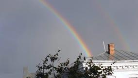 Wolken en een regenboog op het dak stock video