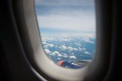 Wolken en hemel zoals die door venster van een vliegtuig wordt gezien Stock Afbeeldingen