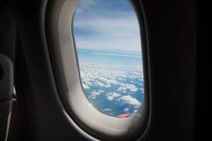 Wolken en hemel zoals die door venster van een vliegtuig wordt gezien Stock Afbeelding