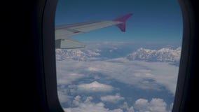 Wolken en Himalayagebergte onder de vleugel van een vliegtuig stock video
