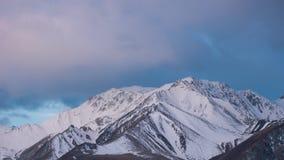 Wolken en Sneeuw behandelde bergen die licht timelapse worden stock footage