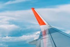 Wolken, hemel en vleugelvliegtuig zoals die door venster van een vliegtuig wordt gezien stock afbeelding