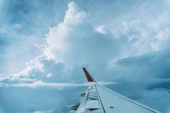 Wolken, hemel en vleugelvliegtuig zoals die door venster van een vliegtuig wordt gezien stock foto's