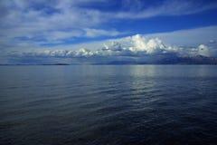 Wolken, hemel, water, en bergen stock afbeelding