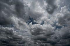 Wolken mit Hintergrund, Sonnenlicht durch sehr dunklen Wolkenhintergrund der dunklen Sturmwolke Lizenzfreies Stockfoto