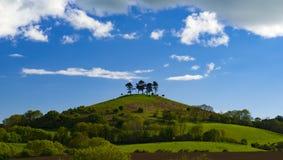 Wolken over de boom bedekte Heuvel van Colmer, Dorset stock afbeeldingen