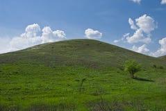 Wolken over de groene heuvel Stock Fotografie
