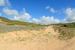 Wolken over een groene heuvel stock foto