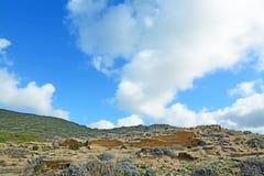 Wolken over een groene heuvel stock afbeelding