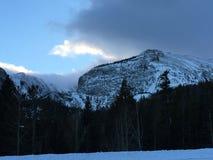 Wolken over sneeuw afgedekte bergpieken stock afbeeldingen