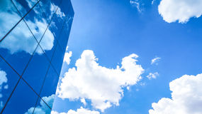Wolken reflektierten sich in den vielen widergespiegelten Facetten eines modernen Büros Lizenzfreie Stockfotos