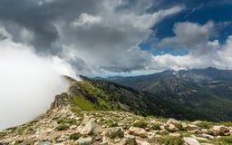 Wolken treffen die Spitze eines Gebirgsrückens auf GR20 in Korsika Lizenzfreies Stockfoto