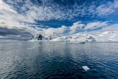 Wolken umgeben die antarktischen Halbinselberge, die im frischen Schnee bedeckt werden Lizenzfreies Stockfoto