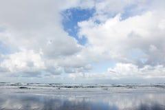 Wolken und blauer Himmel reflektierten sich im nassen Strand Stockbilder