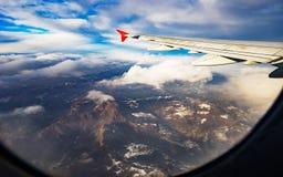 Wolken und Himmel als gesehenes durch Fenster eines Flugzeuges Lizenzfreie Stockbilder