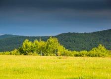 Wolken unter Bergen und Sonnenlichtung Kontrast von Farben Stockbild