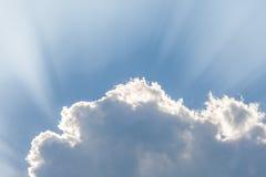 Wolken unter Sonne und Sonnenstrahl durch Wolken Stockfotografie