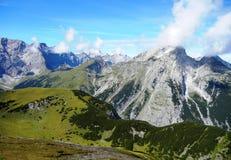 Wolken wat betreft bergpieken in Alpen stock afbeelding