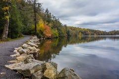 Wolken werden in einem ruhigen Minnewaska See im Orange County, NY reflektiert, umgeben durch hellen Herbstlaub an einem teils be Lizenzfreies Stockfoto