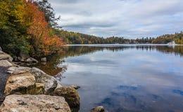 Wolken werden in einem ruhigen Minnewaska See im Orange County, NY reflektiert, umgeben durch hellen Herbstlaub an einem teils be Stockfotos