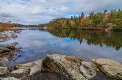 Wolken werden in einem ruhigen Minnewaska See im Orange County, NY reflektiert, umgeben durch hellen Herbstlaub an einem teils be Lizenzfreie Stockfotografie