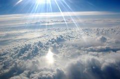 Wolken, zon, hemel zoals die door venster van een vliegtuig wordt gezien Stock Foto