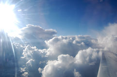 Wolken, zon, hemel zoals die door venster van een vliegtuig wordt gezien Stock Afbeelding