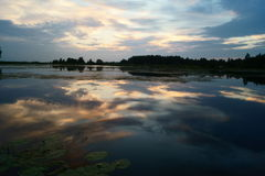 Wolken in zonsondergang dichtbij vijver, Litouwen Royalty-vrije Stock Foto's