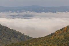 Wolken zwischen den Bergen Stockfoto