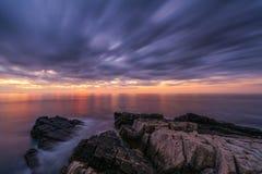 Wolkenbeweging bij zonsopgang over een rotsachtige kustlijn stock afbeeldingen