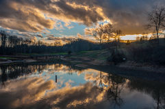 Wolkenbezinning over Meer bij Golfcursus met Brug Stock Foto