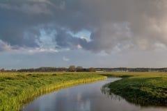 Wolkenhimmel über Fluss im niederländischen Ackerland Lizenzfreies Stockbild