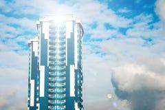 Wolkenkrabber met een glasvoorgevel tegen een heldere blauwe hemel met voorgestelde wolken Royalty-vrije Stock Fotografie