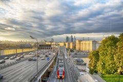 Wolkenkrabbers, Derde Ring Road en ES2G Lastochka & x28; Swallow& x29; treinen op de Centrale de Cirkellijn van Moskou bij zonson stock foto
