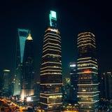 Wolkenkrabbers en bureaugebouwen bij nacht in Shanghai Stock Fotografie