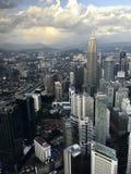 Wolkenkrabbers en torens van Petronas, de hoofdstad van Maleisië, Kuala Lumpur tegen de achtergrond van bergen en hemel met wolke royalty-vrije stock afbeelding