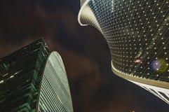 Wolkenkrabbers tegen de donkere hemel twee high-rise gebouwen, de nachthemel Moderne bureaugebouwen stock afbeelding