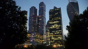 Wolkenkrabbers van het commerciële centrum bij nacht Mening van achter boomtakken stock videobeelden