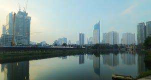 Wolkenkrabbersbouw op rivieroever in Djakarta stock videobeelden