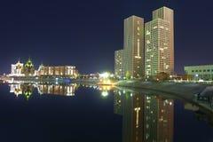 Wolkenkratzer und Reflexion im nächtlichen Fluss Stockfotografie