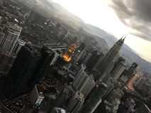 Wolkenkratzer und Türme von Petronas, die Hauptstadt von Malaysia, Kuala Lumpur, gegen den Hintergrund von Bergen und von Himmel  stockfoto