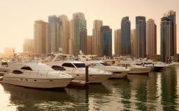 Wolkenkratzer und Yachten in Dubai Marina During Sunset lizenzfreie stockbilder