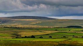 Wolkenvorming over heuvels en landbouwbedrijven stock afbeeldingen