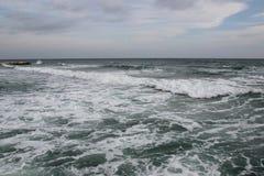 Wolkiges Wetter Goldener Sand, Wellen und Schaum Bewölkter Tag auf dem sandigen Strand Panoramablick des schönen sandigen Strande lizenzfreies stockfoto