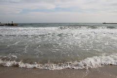 Wolkiges Wetter Goldener Sand, Wellen und Schaum Bewölkter Tag auf dem sandigen Strand Panoramablick des schönen sandigen Strande lizenzfreie stockfotografie